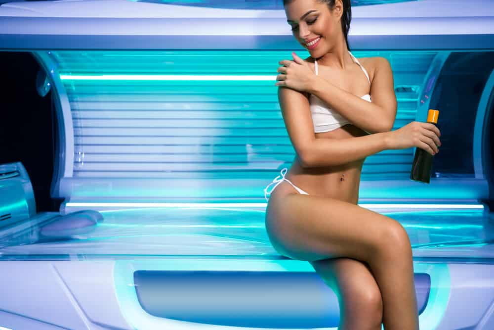 Attractive young woman preparing for tanning in solarium