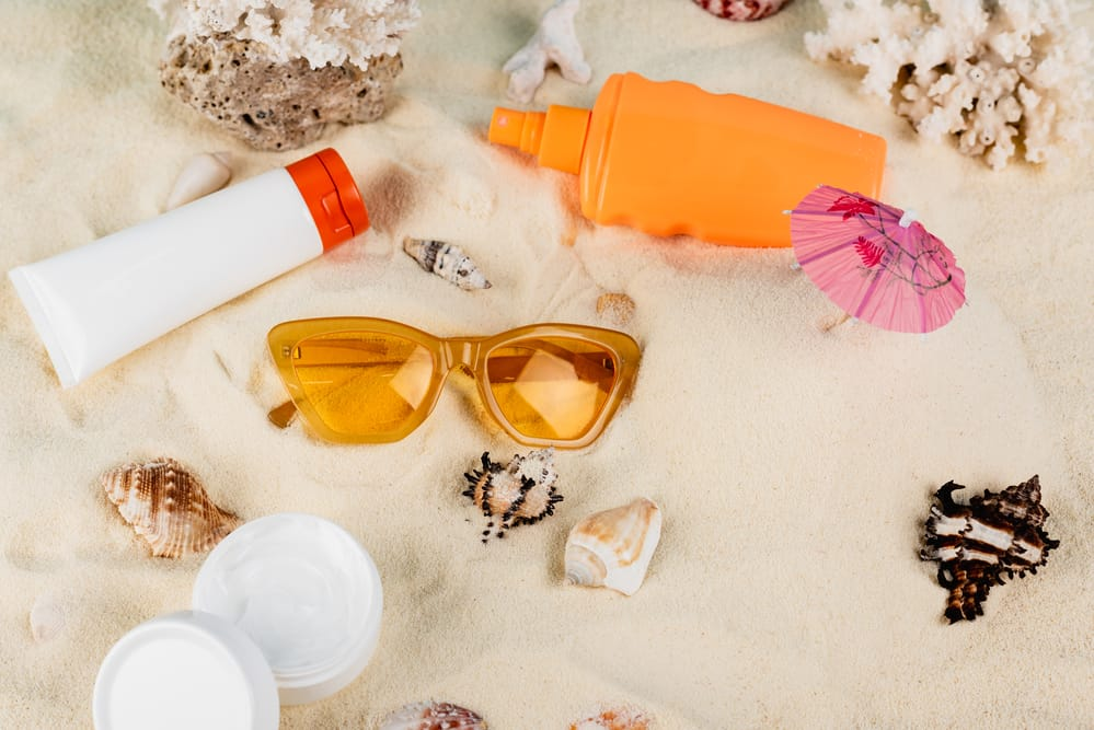 Top view of containers with sunscreen and cosmetic cream