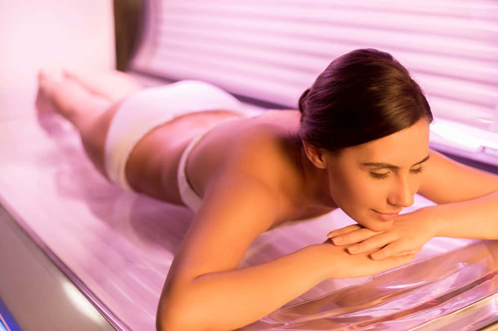 woman lying on tanning bed and smiling