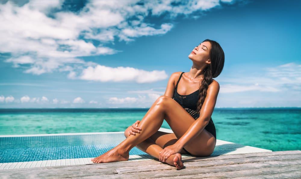 woman posing sunbathing tanning in black one piece bathing suit